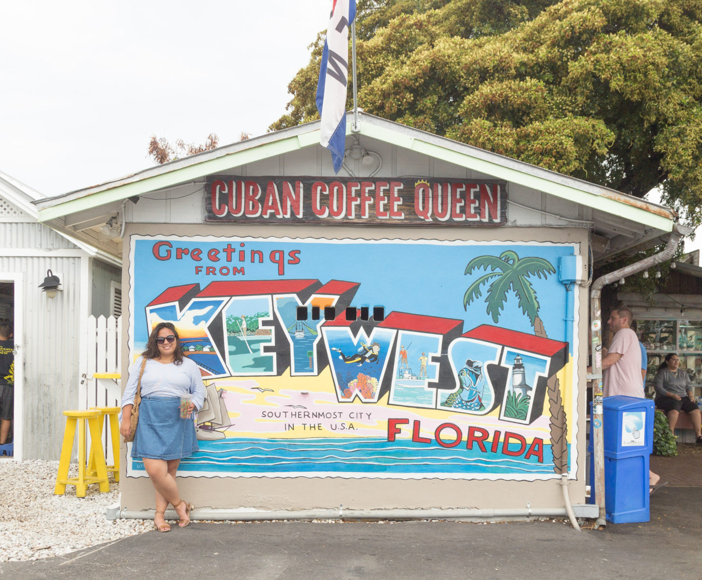 Me standing in front of a Greetings from Key West Florida sign at Cuban Coffee Queen
