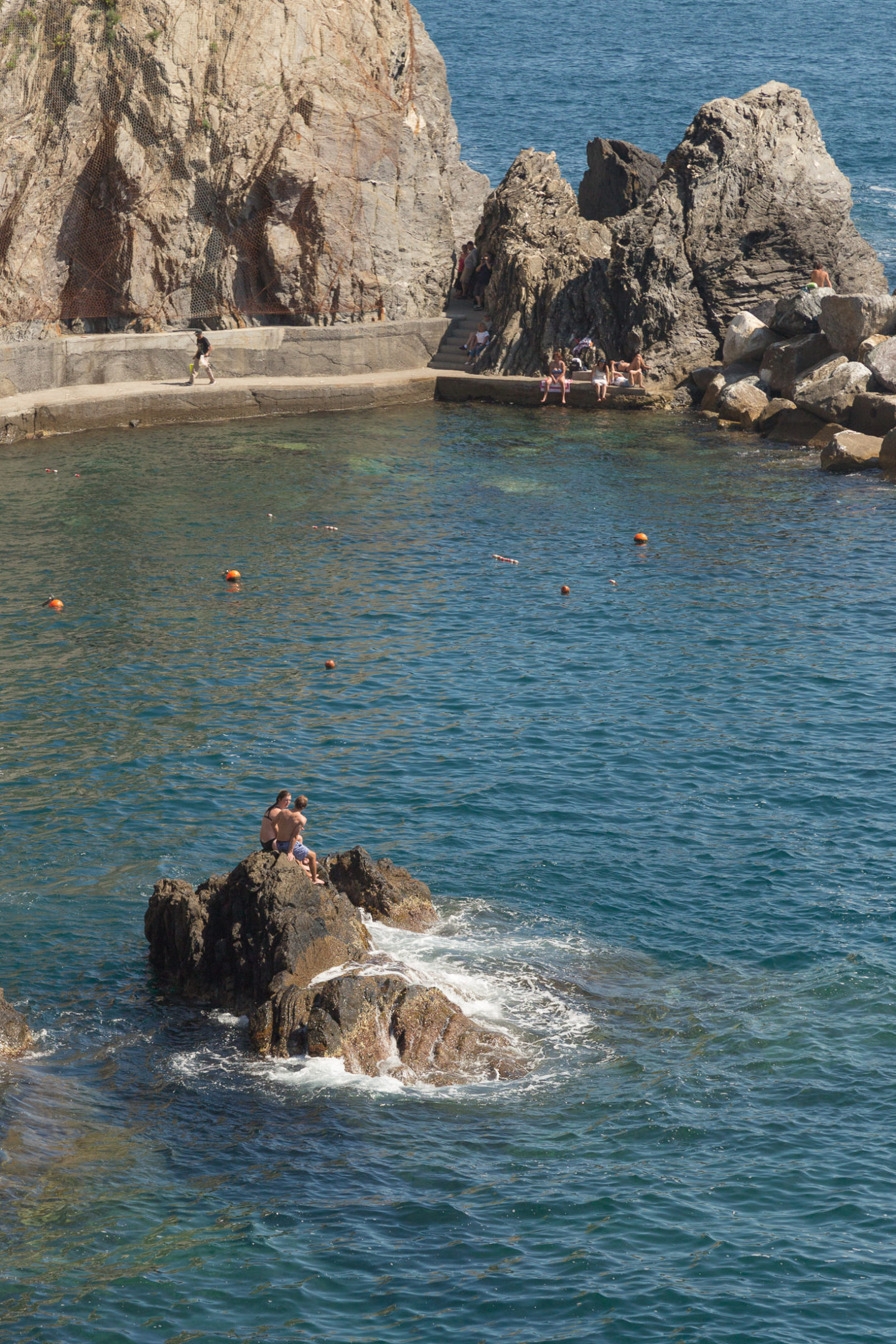 couple sitting on rock in blue water