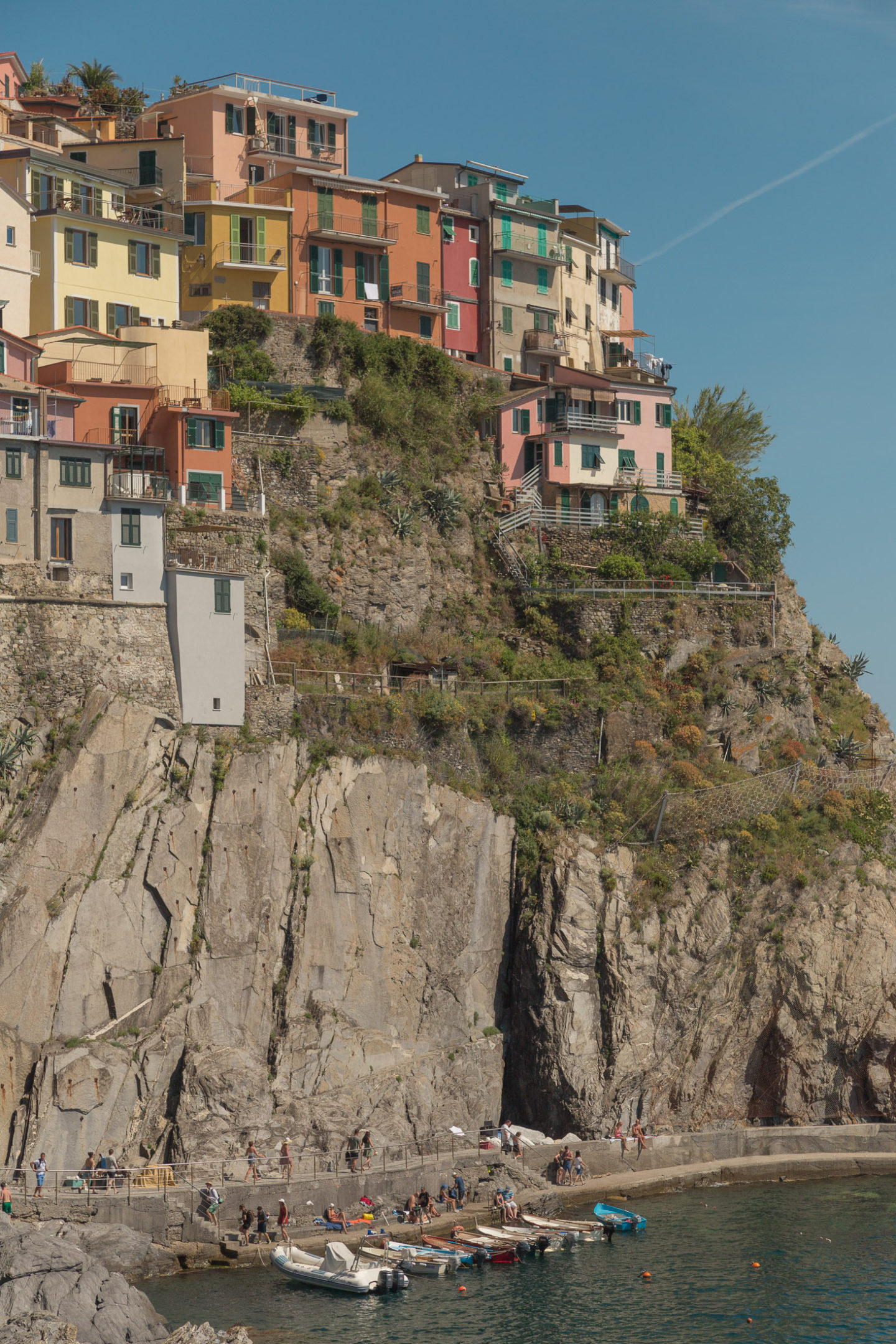 colorful buildings on cliffside with some rowboats at bottom