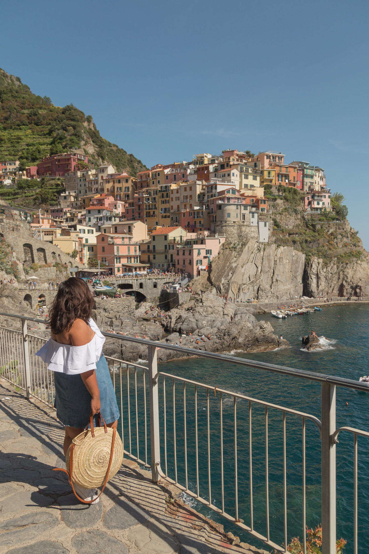 girl in white top and jean skirt with straw circle bag standing behind fence and looking at panoramic view of colorful buildings on cliffside in manarola