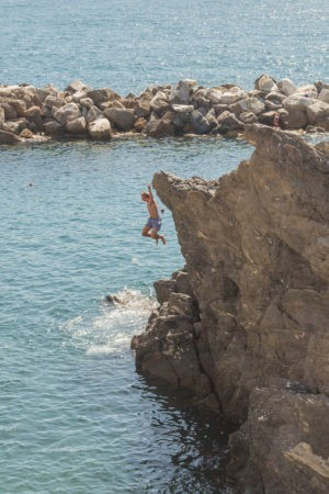 boy jumping from cliff in swimming area in manarola