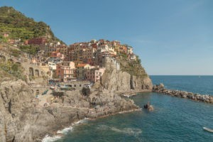 panoramic view of manarola where you can see the colorful buildings sitting on the cliff over the blue water