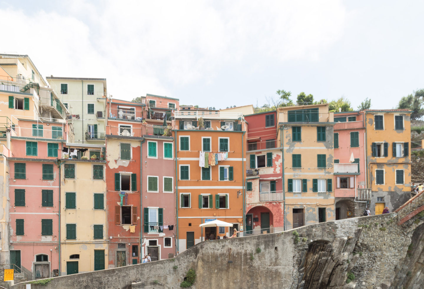 colorful buildings atop of a cliff -- most prominent color is orange