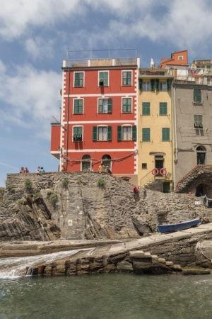 reddish building in riomaggiore right at edge of rocks