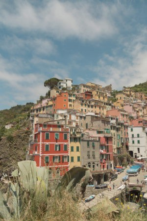 Riomaggiore in Cinque Terre - colorful buildings in tiers with a blue sky, most prominent building is red