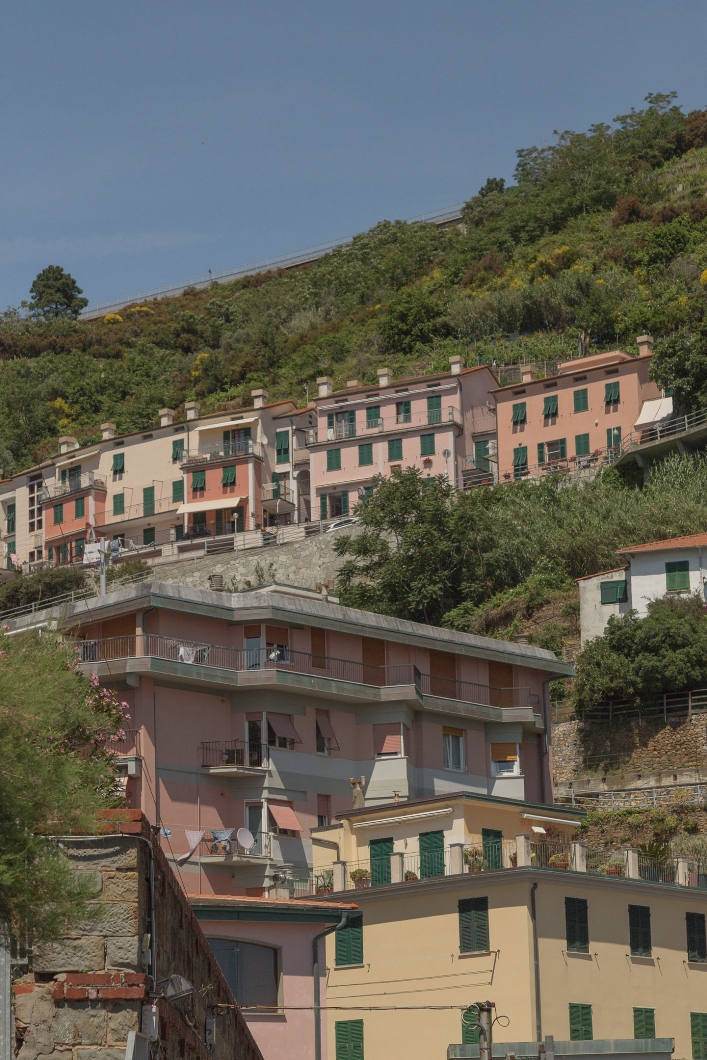 pinkish pastel buildings against green hill and blue sky