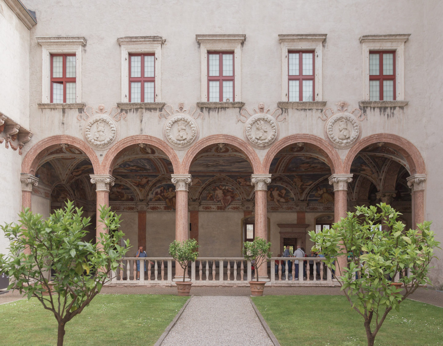 courtyard in castle -- 5 rounded arches with faded red boarders and 4 circle impressions on wall. Above them are 5 rectangle windows split into 4 panes, also a red boarder. In the fore front is a path and green grass with two small trees