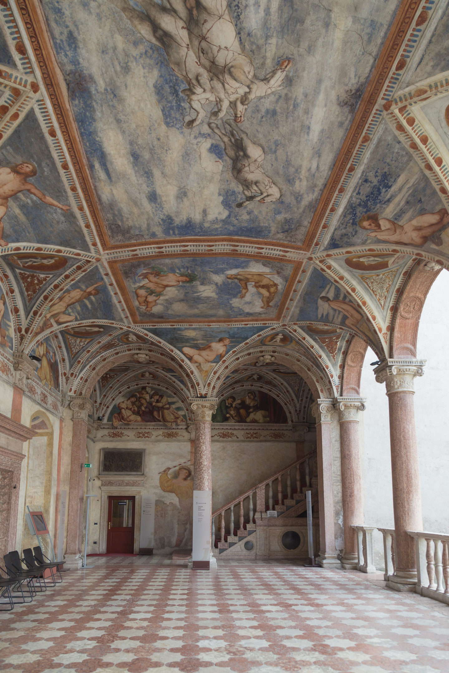 ceiling in Trento castle -- top is all painting with a lot of blue and then two arches and a tiled floor