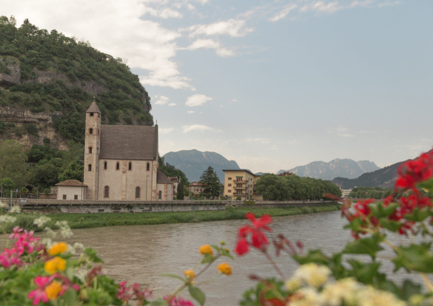 view of river in Trento with red, yellow, and pink flowers in forefront and a stone house in the background