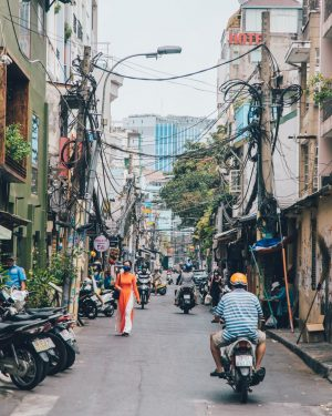 Woman in an ao dai walking in alley near the Pink Cathedra